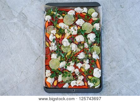 Cut assorted vegetables on a baking sheet on marble background