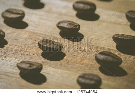 close up image of many coffee beans on wood