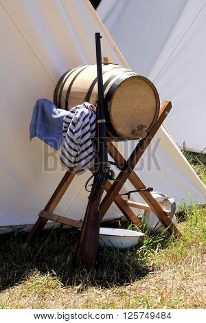 Rifle leaning against a wooden water barrel at a Civil War