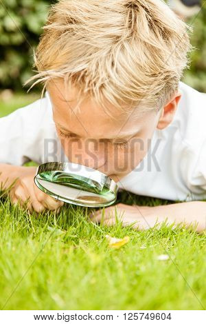 Close Up Of Boy Using Magnifying Glass Outside