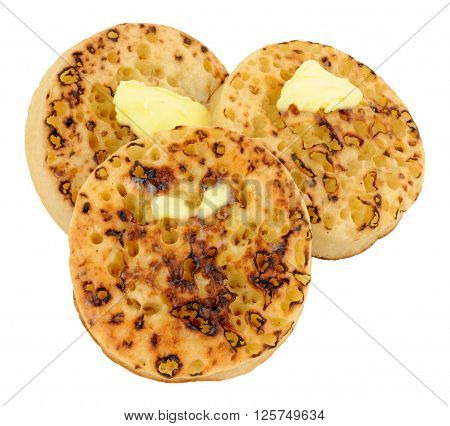 Toasted English crumpets with melting butter isolated on a white background