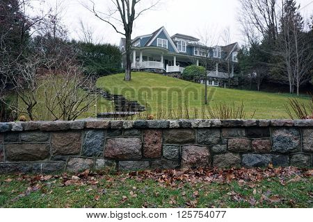 HARBOR SPRINGS, MICHIGAN / UNITED STATES - DECEMBER 23, 2015: A stone wall in front of a lakefront mansion along Glenn Drive in Harbor Springs, Michigan.
