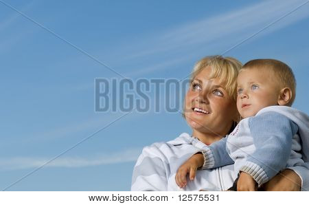 Happy Mother and Baby outdoor.Over Clear Blue Sky