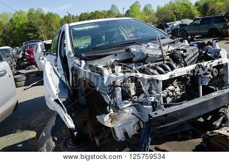 Charlotte, NC, United States - April 14, 2016: Serious damaged car close up on a junk yard