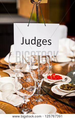 White judges sign hanging at dining table.