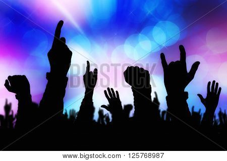 Silhouettes of concert crowd hands supporting band performing live music on stage young people on rock gig enjoying.