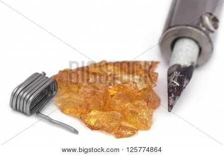 Soldering iron with spool of solder and resin over white background