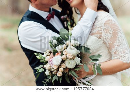 Beautiful wedding bouquet in hands of the bride near groom.
