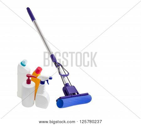 Blue plastic mop with aluminium handle mounting clamp and a sponge and several different bottles of cleaning agents on a light background