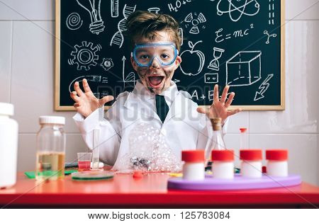 Portrait of happy little scientist with glasses and dirty face opening his arms behind of glass with soap foam over table