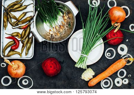 Onion, beet, pepper, garlic, carrot, cabbage ready to prepare salad. Detox and diet food. Composition of organic veggies. Vegetable food background. Red and green veggies composition on a black table.