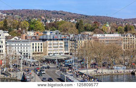 Zurich, Switzerland - 10 April, 2016: pedestrians and traffic on Quaibruecke bridge and Bellevue square, view from the Ferris wheel temporarily installed on Burkliplatz square. Zurich is the largest city in Switzerland.