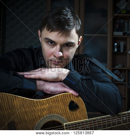 Portrait of wistful young man with guitar.