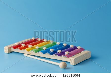 colourful child's glockenspiel with mallets on blue