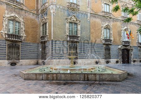 Valencia Spain - May 18 2014: Fountain and part of the Ornate Alabaster Stone facade of the historic Palace of Marques de Dos Aguas in Valencia Spain. Now here is the National Ceramics Museum.