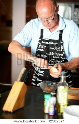 Portrait of a senior man peeling an onion