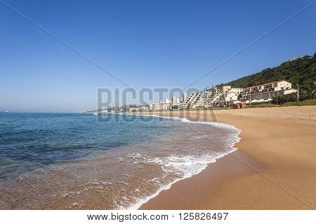 Beach ocean sands waterline with holiday apartments along coastline landscape.