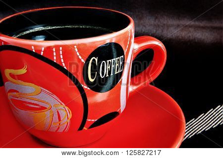 Red cup with coffee against a dark background. A cup with a saucer close up. On a cup letters and drawings are represented. A background of dark brown color with light strips. Indoors. The prevailing color red and dark brown. Blackout at the edges. Photo.