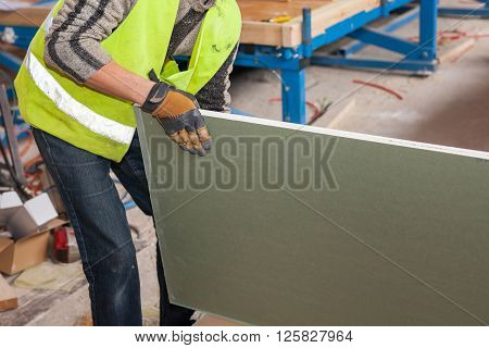 Building a wall for frame house. Worker holding a drywall