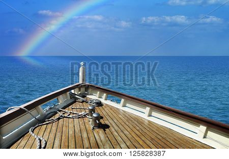 Ship in a calm sea. Rainbow on the horizon.