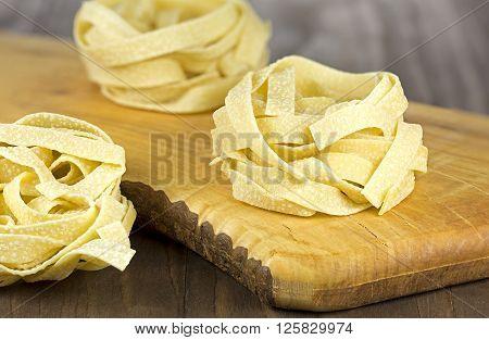 Tuscany durum wheat semolina pasta on wooden background