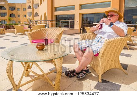 MARSA ALAM, EGYPT, MARCH 28, 2016:  Senior tourist enjoys a drink on Three Corners Equinox Beach Hotel terrace in Marsa Alam, Egypt