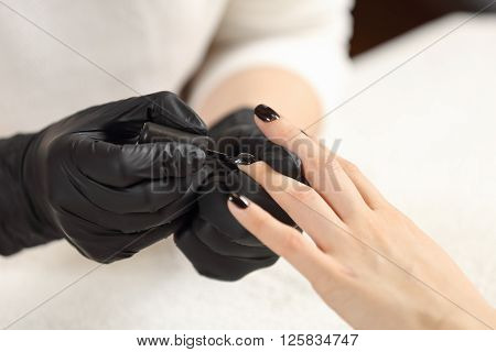 Manicurist paints customer nails in black. Top view manicurist holds customer hands.