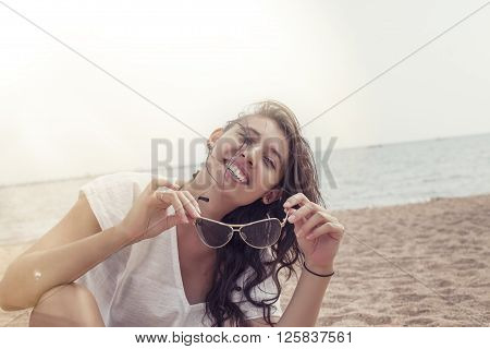 Woman In A Tunic On The Beach Happy Smiles And Relaxes In The Sunlight