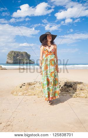brunette adult woman with black hat and big vintage floral dress looking and walking on sand at Ballota beach with ocean and island behind in Asturias Spain