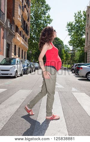 brunette brown hair pregnant woman with red shirt green trousers in summer walking on crosswalk in Madrid urban street