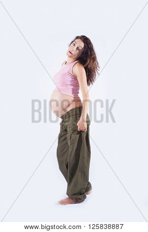 eight month pregnant brunette brown hair woman naked paunch pink shirt green trousers standing and looking isolated over white background