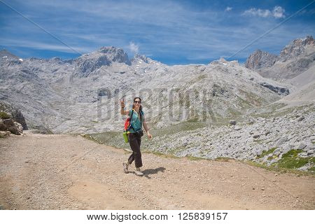 brunette sport woman with green shirt brown trousers walking or hiking or trekking on rural path in Picos de Europa mountains in Cantabria Spain gesturing victory symbol with finger hands