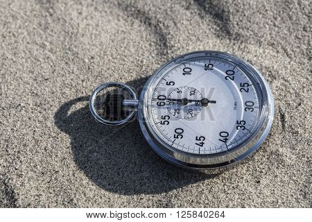 analog Stopwatch on wet sea sand abstract time pass