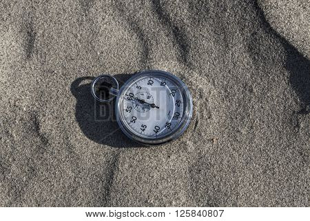 Analog Stopwatch on wet sea sand abstract time
