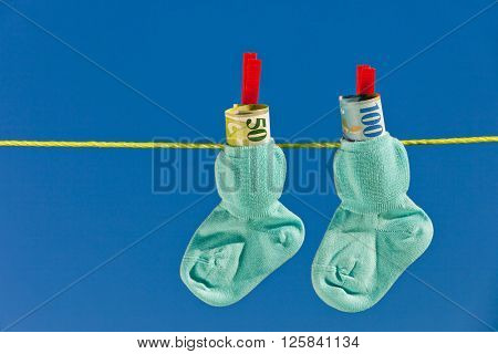 baby socks on clothesline with swiss francs