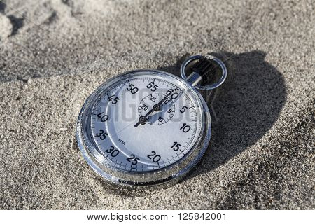 analog Stopwatch on wet sea sand closeup