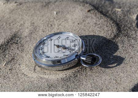 analog Stopwatch on wet sea sand close-up