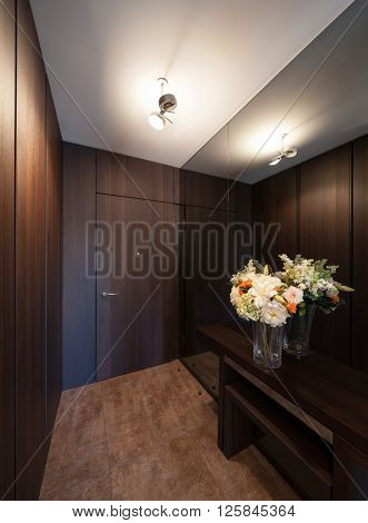 Interiors of new apartment, lobby with a beautiful vase of flowers, wooden walls and mirror