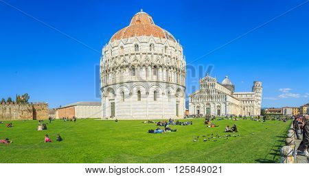 PISA, ITALY - MARCH, 24, 2016:Tourists from all over the world admire the ancient Italian architectureworldwide for its unintended tilt.