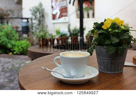 Cup of cappuccino with pansies in a pot on the table. White cup of coffee with spoon on the table outside terrace. Yellow pansies pot aside. Small Italian terrace and patio.