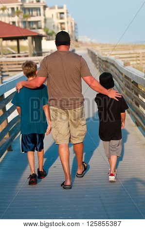 Dad walking with his two boys with arms around their shoulders.