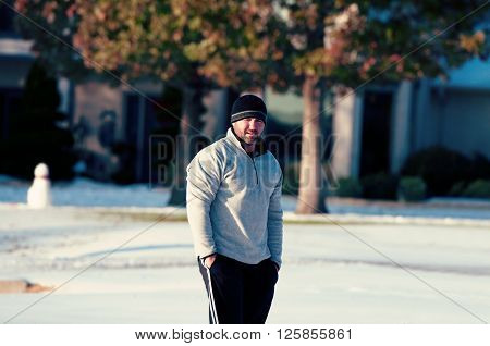 Man in toboggan standing in snow looking at camera in a residential neighborhood.