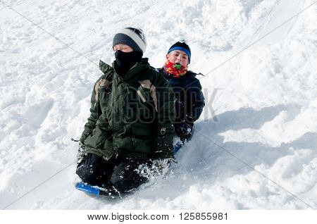 Two cute boys sledding down a snowhill.