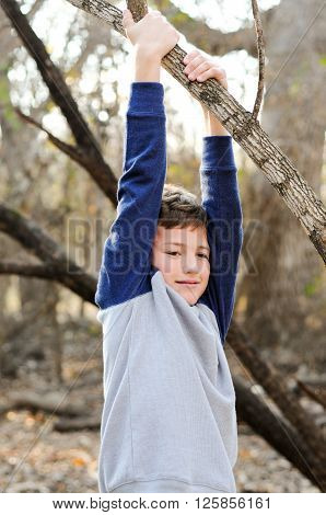 Outdoor portrait of young handsome boy hanging from a branch of a tree.