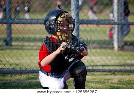 Youth baseball catcher with a glove during a game.