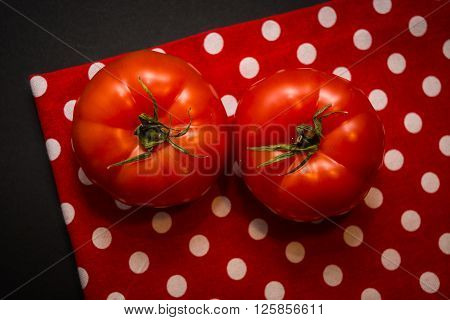 Two red tomatoes lying on the red tea-towel and black background