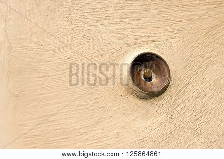 Old brass doorbell button on a beige wall in Portovenere or Porto Venere (UNESCO world heritage site) - La Spezia Liguria Italy