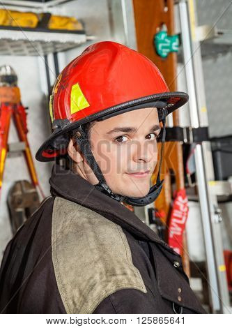 Confident Male Firefighter Against Firetruck