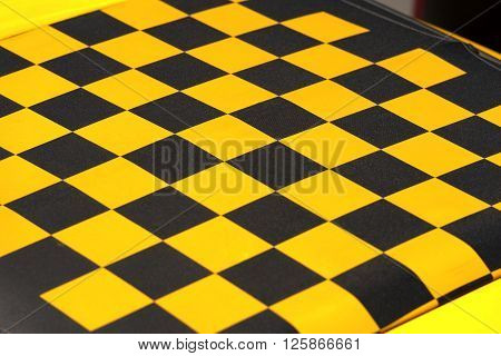 Detail of the roof of a car yellow and black checkered. Fabric sunroof