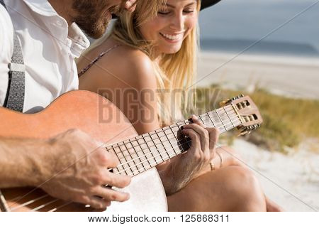 Close up of young man playing an acoustic guitar on the beach. Happy couple playing guitar on beach in love. Smiling woman listening to man playing guitar at beach.
